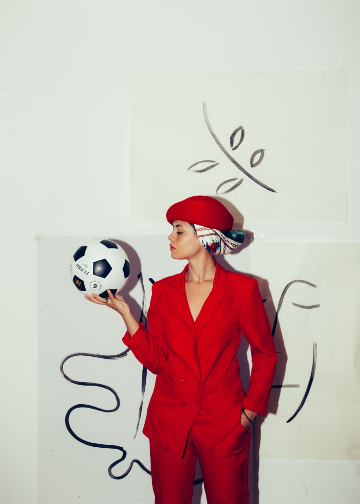 woman-in-red-blazer-holding-white-and-black-soccer-ball-3819644